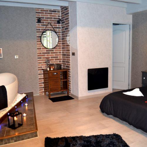 salle de bain ouverte de la chambre dionysos avec baignoire face au lit
