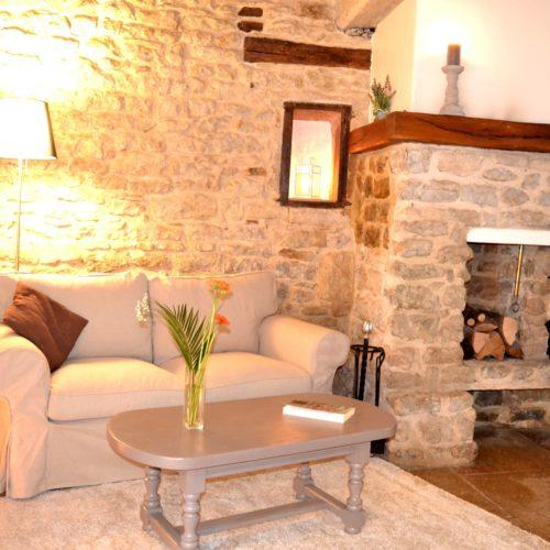 coin détente de la table d'hôtes avec cheminée à l'âtre et canapé