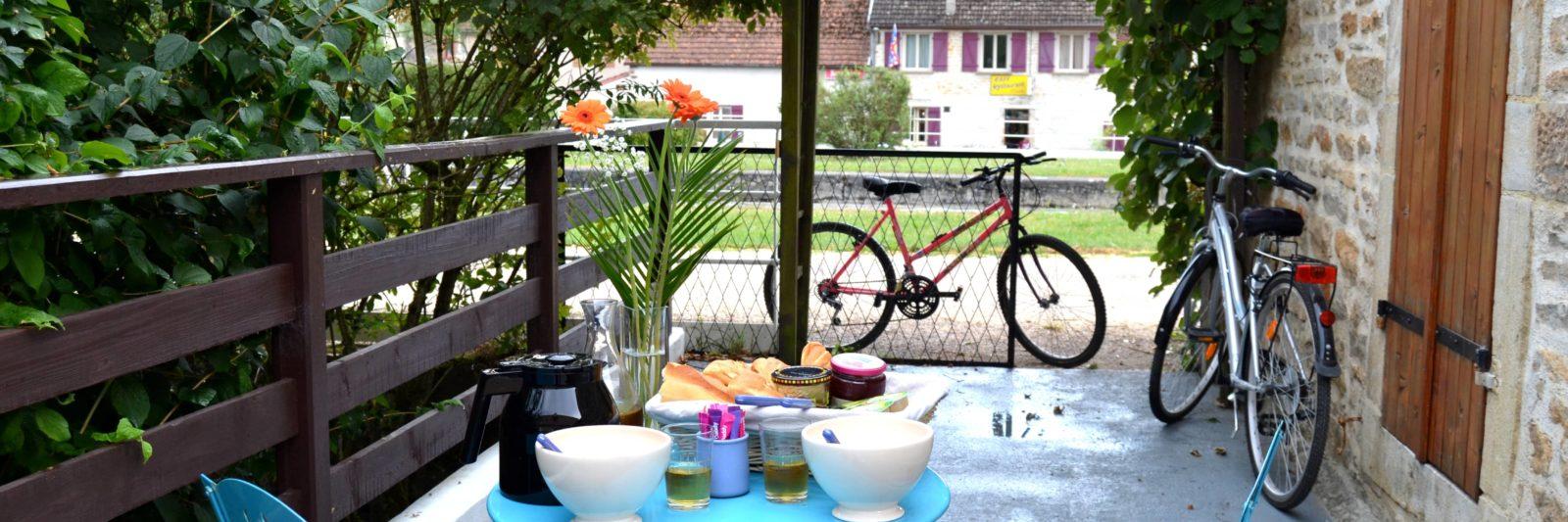 terrasse avec table et chaises ainsi que la piste cyclable du canal de Bourgogne